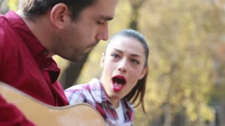 Close-up of young brunette woman singing while man playing guitar next to her