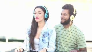 Close up of young couple having fun listening to music with headphones and dancing on nice sunny day, graded