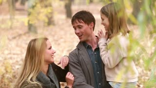 Close up of young family standing in park and talking, father carries daughter in his arms