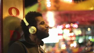 Close up of young man shaking his head to the rhythm of music with headphones at amusement, park