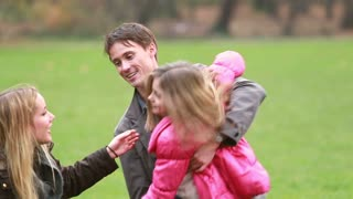 Close up of young parents playing with daughter in park in autumn
