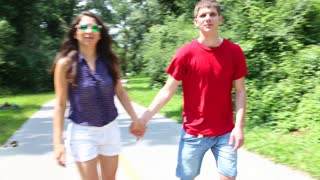 Close up of young woman and man rollerblading on a sunny day in park, holding hands.