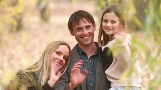 Close up portrait of beautiful young family smiling and waving in park