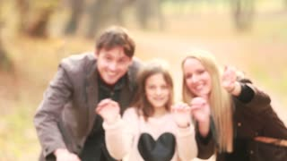Close up portrait of beautiful young family waving in park, graded
