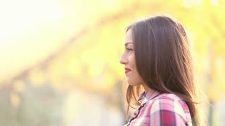 Close-up profile of a young beautiful brunette woman singing, in slow motion, graded