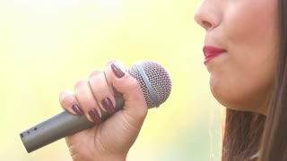 Close-up profile of beautiful woman's mouth with red lipstick, smiling and singing with microphone, graded