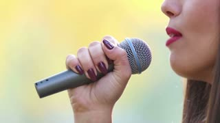 Close-up profile of beautiful woman's mouth with red lipstick, smiling and singing with microphone, in slow motion