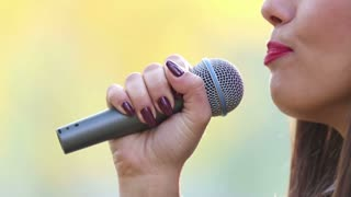 Close-up profile of beautiful woman's mouth with red lipstick, smiling and singing with microphone