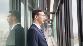 Close up profile of handsome smiling businessman standing by the window with city view
