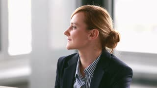 Close up profile of young businesswoman listening and nodding during corporate presentation, graded