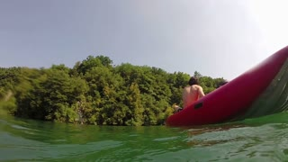 Close up Split shot of a young man swimming towards his friend in a canoe, in slow motion
