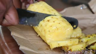 Close up view of a local man cutting pineapple, a very popular fruit which grows all around Sri Lanka.