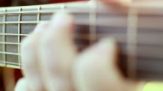 Close-up view of hand playing classical guitar, graded in slow motion