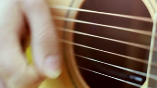 Close-up view of hand playing classical guitar, graded
