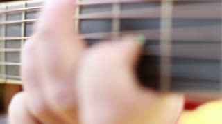 Close-up view of hand playing classical guitar