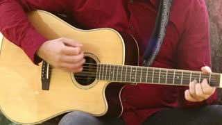 Close-up view of man hands playing acoustic guitar, graded