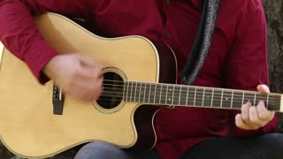 Close-up view of man hands playing acoustic guitar