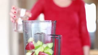 Close view of hand pouring water into blender for fruit shake, slow motion, graded