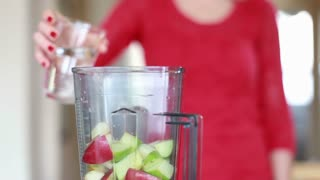 Close view of hand pouring water into blender for fruit shake