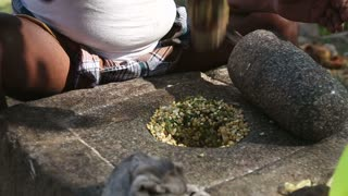 Close view of man sitting and grinding seeds on a traditional grinding stone.