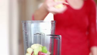 Close view of woman hand putting pieces of fruit into blender for smoothie, graded