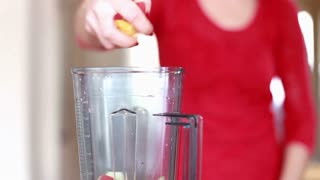 Close view of woman hand putting pieces of fruit into blender for smoothie, in slow motion, graded