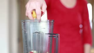 Close view of woman hand putting pieces of fruit into blender for smoothie