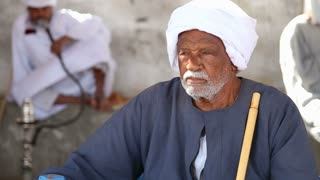 closeup of a egyptian man in traditional clothing sitting on the bench