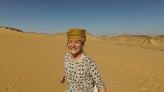 closeup of happy woman running barefoot in desert, Egypt