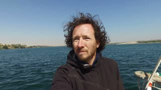 closeup of male tourist standing on bow of felucca while sailing on Nile