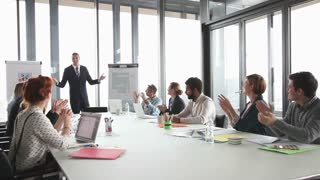 Colleagues applauding director during a meeting in conference room