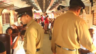 COLOMBO, SRI LANKA - FEBRUARY 2014: Local people traveling in train, while conducters are checking the tickets. The Sri Lankan railway transports millions of people daily in the country.