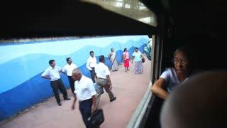COLOMBO, SRI LANKA - MARCH 2014: Woman sitting at window of train passing platform at train station.