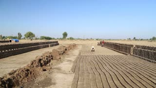 Construction site at field in Jodhpur with arranged rows of bricks.