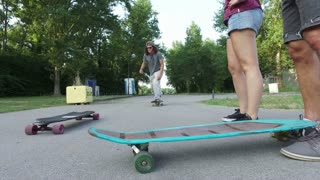 Cool man jumping with skateboard on a friend's longboard