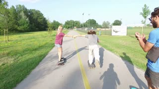 Cool man passing with skate under the arms of other two skateboarders