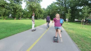 Cool young friends longboarding on sunny day