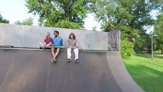 Cool young friends sitting on a ramp at skatepark and chilling