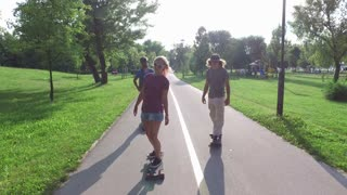Cool young friends skateboarding on sunny day
