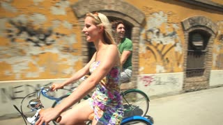 couple cycling in town on sidewalk lane