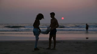 Couple folding towel and hugging at beach in Goa at sunset.