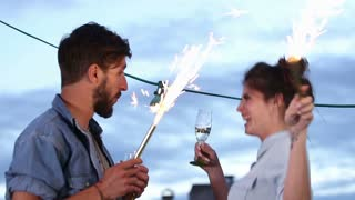 Couple having fun dancing with firework candles
