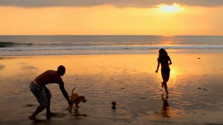 Couple playing on beach with dog at sunset in Bali