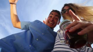 Crazy young couple looking down at camera, drinking cocktails and laughing