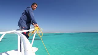 Crew member tidying rope on the boat