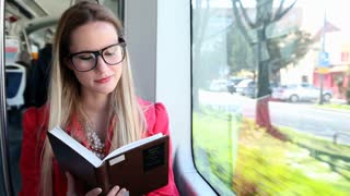 Cute blond woman reading book while driving in tram and looking to camera