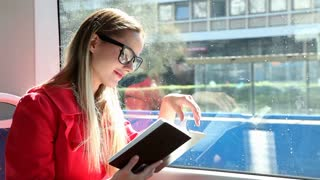 Cute blond woman reading book while riding tram, pointing on page
