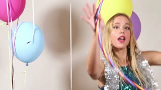 Cute blonde woman playing with hula hoop in photo booth