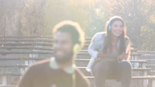 Cute couple with headphones listening to music and dancing to the rhythm  at the park