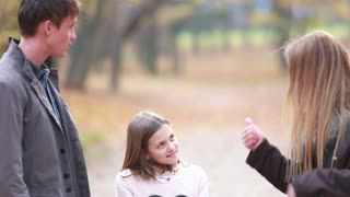 Cute little daughter talking with parents and jumping on the spot in park